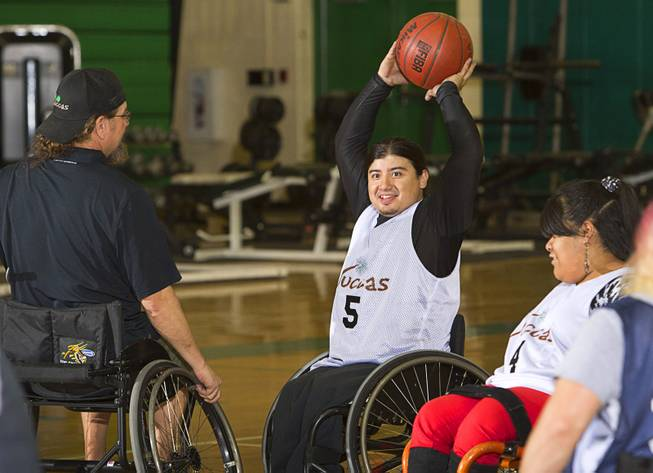 Steven Morales, center, prepares to pass the ball during wheelchair basketball practice at Rancho High School Tuesday, Feb. 25, 2014. The team is practicing for a scrimmage against a Wounded Warriors team at Nellis Air Force Base on Thursday.