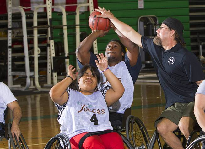 Timothy Oliver gets stuffed by Jonathan Foster, during wheelchair basketball practice at Rancho High School Tuesday, Feb. 25, 2014. Cinthya Huendo is at lower left. Foster works for the City of Las Vegas and helps head the Las Vegas Paralympic Sport Club.