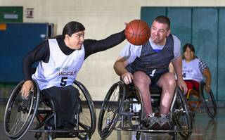 Steven Morales grabs a ball ahead of Marc Fenn during wheelchair basketball practice at Rancho High School Tuesday, Feb. 25, 2014. The team is practicing for a scrimmage against a Wounded Warriors team at Nellis Air Force Base on Thursday.