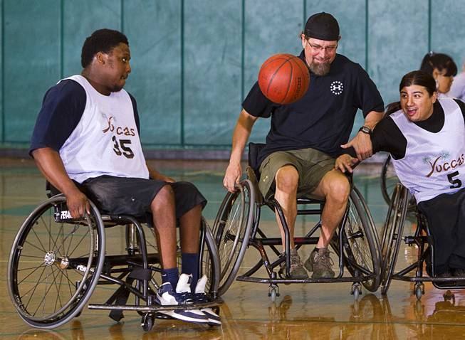 Timothy Oliver, left, Jonathan Foster, center, and Steven Morales go after a loose ball during wheelchair basketball practice at Rancho High School Tuesday, Feb. 25, 2014. Foster works for the City of Las Vegas and helps head the Las Vegas Paralympic Sport Club.