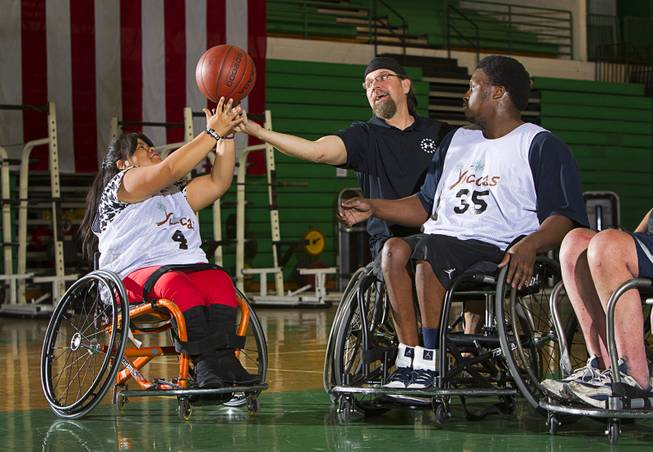 Cinthya Huendo, Jonathan Foster, center, and Timothy Oliver go after a rebound during wheelchair basketball practice at Rancho High School Tuesday, Feb. 25, 2014. Foster works for the City of Las Vegas and helps head the Las Vegas Paralympic Sport Club.