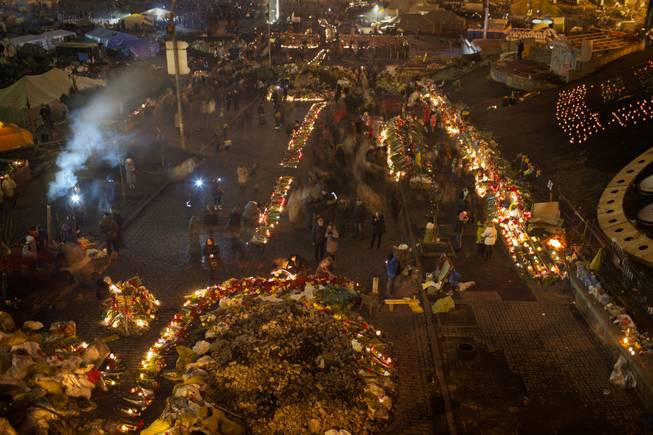 People light cantles and place flowers at a memorial for the people killed in clashes with the police at Kiev's Independence Square, the epicenter of the country's current unrest, Ukraine, Tuesday, Feb. 25, 2014.