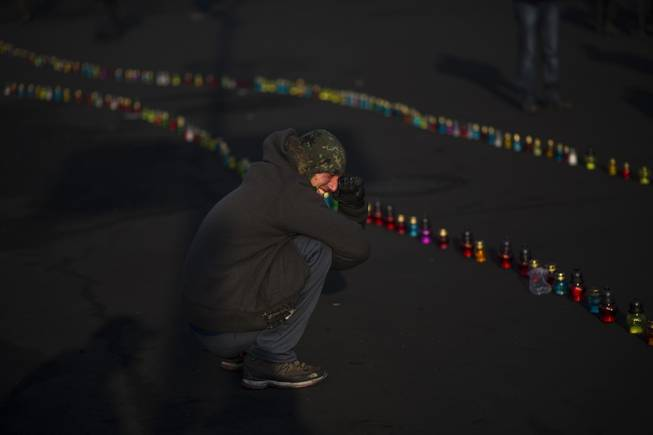 An opposition supporter cries near to a memorial for the people killed in clashes with the police at Independence Square in Kiev, Ukraine, Monday, Feb. 24, 2014.