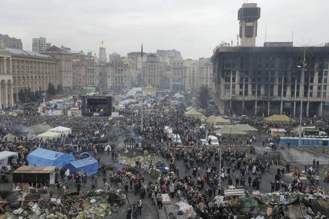 General view of Kiev's Independence Square, the epicenter of the country's recent unrest, Ukraine, on a mourning day  Sunday, Feb. 23, 2014. Official reports say 82 person were killed in severe clashes between opposition activists and riot police. A destroyed trade union house which was burned in clashes seen in the background right.