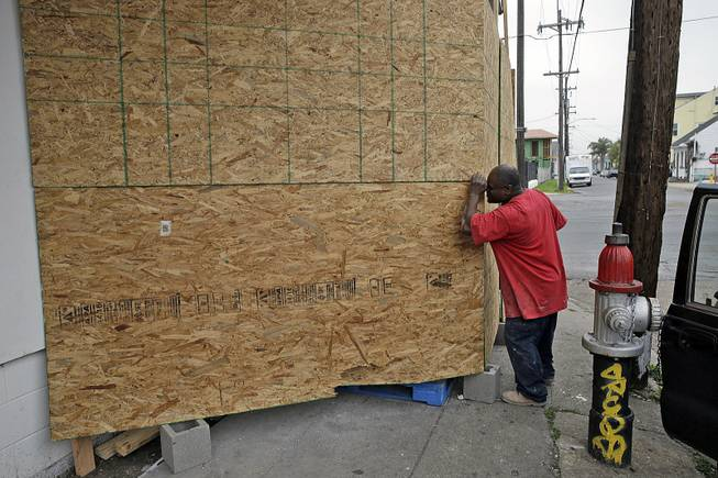 A passer-by peers into a plywood barrier now protecting a mural by the artist Banksy, in New Orleans, Tuesday, Feb. 25, 2014.