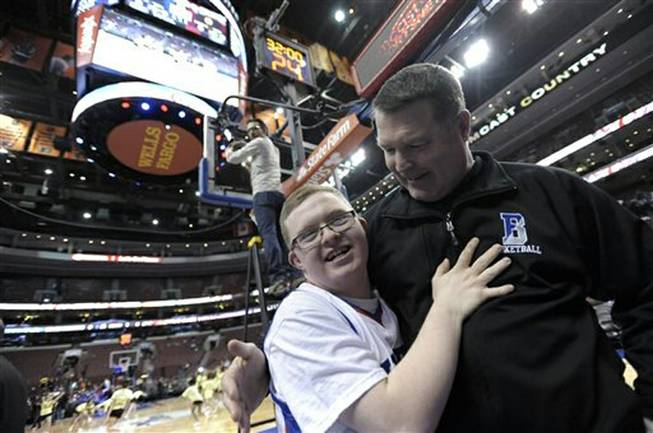 Kevin Grow hugs his Bensalem High basketball coach John Mullin before an NBA game between the Philadelphia 76ers and the Cleveland Cavaliers on Tuesday, Feb. 18, 2014, in Philadelphia. Kevin had been signed by the Philadelphia 76ers to a ceremonial two-day contract. Next, he'll play with the Harlem Globetrotters.