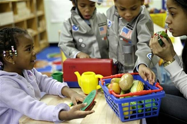 Oumou Balde, 4, left, plays with her teacher Jacqualine Sanchez, right, and pretend food in a pre-kindergarten class at the Sheltering Arms Learning Center in New York in a program to educate children about nutrition and health.