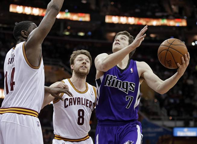 Sacramento Kings' Jimmer Fredette (7) goes in for a shot against Cleveland Cavaliers' Henry Sims, left, and Matthew Dellavedova (8), from Australia, during the second quarter of an NBA basketball game Tuesday, Feb. 11, 2014, in Cleveland.