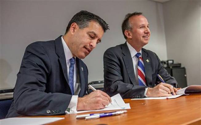 Nevada Gov. Brian Sandoval and Delaware Gov. Jack Markell sign a multistate Internet gaming agreement Tuesday, Feb. 25, 2014, in Wilmington, Del. The agreement establishes a legal framework allowing residents of the two states to play online poker against each other. The agreement also allows other states to join the agreement with the approval of existing members.