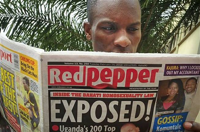 "A Ugandan reads a copy of the Red Pepper tabloid newspaper in Kampala, Uganda Tuesday, Feb. 25, 2014. The Ugandan newspaper published a list Tuesday of what it called the country's ""200 top"" homosexuals, outing some Ugandans who previously had not identified themselves as gay, one day after Uganda President Yoweri Museveni enacted a harsh anti-gay law."