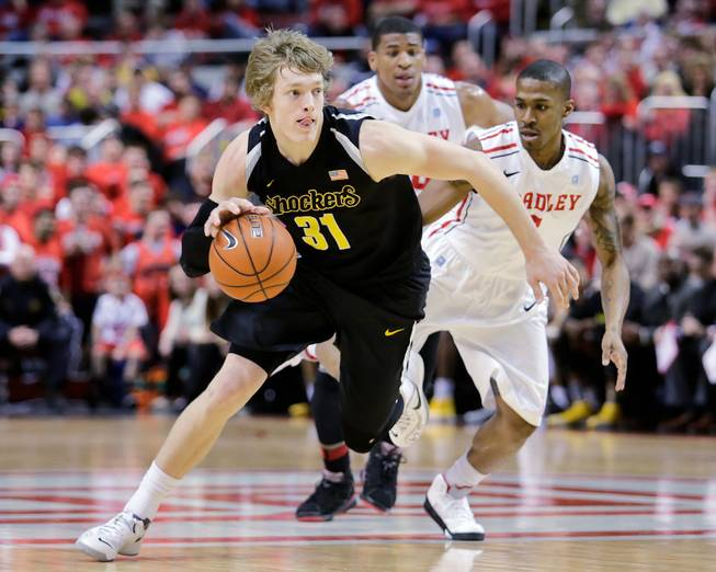 Wichita State guard Ron Baker (31) pushes down the court past the defense of Bradley guard Ka'Darryl Bell (0) during the first half of an NCAA college basketball game at Carver Arena, Tuesday, Feb. 25, 2014, in Peoria, Ill.