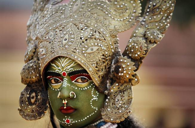 A women dressed as Hindu Goddess Kali participates in a procession on the eve of Shivratri festival, in Jammu, India, Wednesday, Feb. 26, 2014.