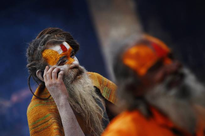 A Hindu holy man speaks on his cell phone in the courtyard of the Pashupatinath Temple in Katmandu, Nepal, Wednesday, Feb. 26, 2014.