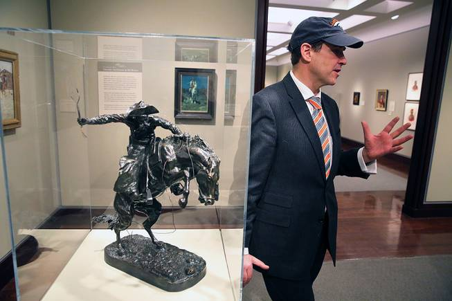 Denver Art Museum Director Christoph Heinrich speaks with a reporter as he leans against a Frederic Remington bronze statue of a cowboy riding a bucking horse, part of a collection on display inside the Denver Art Museum, Monday, Jan. 27, 2014.