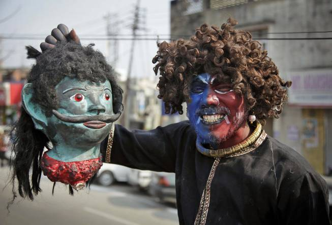 A Hindu devotee dressed as a demon participates in a procession on the eve of Shivratri festival, in Jammu, India, Wednesday, Feb. 26, 2014.