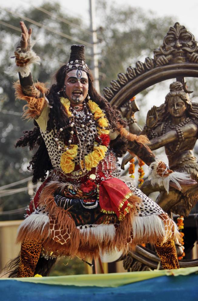 A devotee dressed as Hindu God Shiva dances as he participates in a procession on the eve of Shivratri festival, in Jammu, India, Wednesday, Feb. 26, 2014.