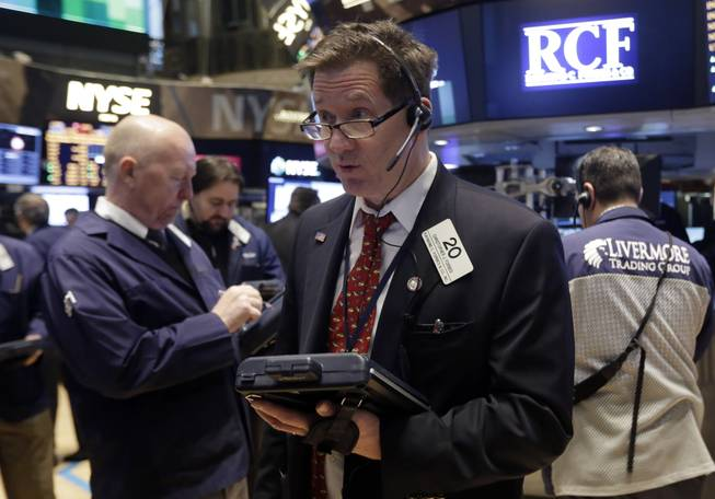 In this Wednesday, Feb. 26, 2014, file photo, Trader Christopher Forbes, center, works on the floor of the New York Stock Exchange.