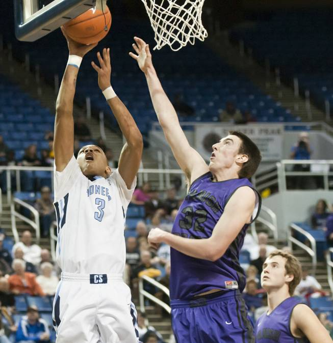 Jordan Davis forces in a layup over Jake Keady Thursday, Feb. 27, 2014 as Canyon Springs defeats Spanish Springs 66-51 in the semifinals of the Nevada State Championships at Lawlor Events Center in Reno.