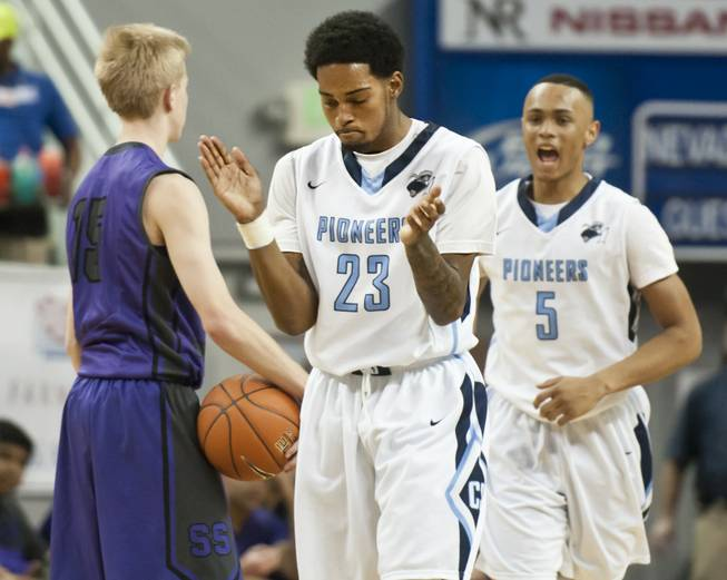 Shaquille Carr, center, celebrates after forcing a traveling call as teammate Gerad Davis approaches from behind Thursday, Feb. 27, 2014 as Canyon Springs defeats Spanish Springs 66-51 in the semifinals of the Nevada State Championships at Lawlor Events Center in Reno.