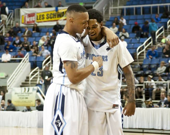 Shaquile Carr, right, shares a hug with a teammate after the final buzzer as Canyon Springs defeats Spanish Springs 66-51 in the semifinals of the Nevada State Championships at Lawlor Events Center in Reno, Thursday, Feb. 27, 2014.