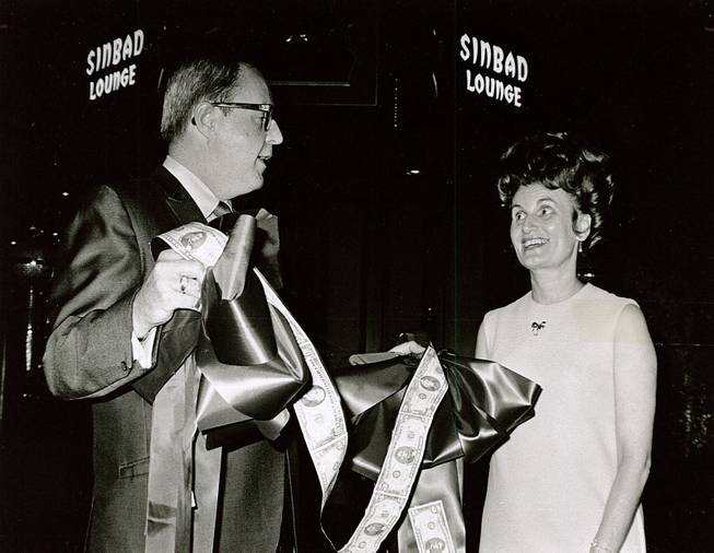 Ralph Griswold, comptroller of the Aladdin Hotel, presents a unique money ribbon that was used in ceremonies marking the opening of the newly built Sinbad Lounge at the Aladdin to Kitty Rodman, first vice president of the Easter Seal Society for Crippled Children, Aug. 12, 1969.