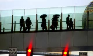 Some pedestrians carrying umbrellas, cross a foot bridge over Las Vegas Blvd. on Friday, Feb. 28, 2014.