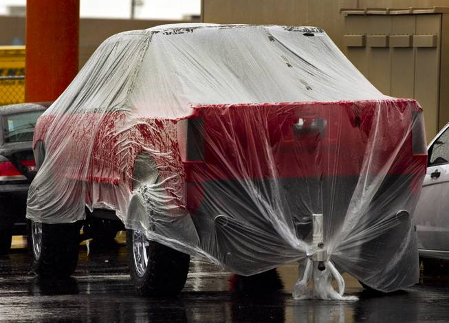 A newly painted vehicle is wrapped in plastic to keep it dry during a rainy day in Las Vegas on Friday, Feb. 28, 2014.