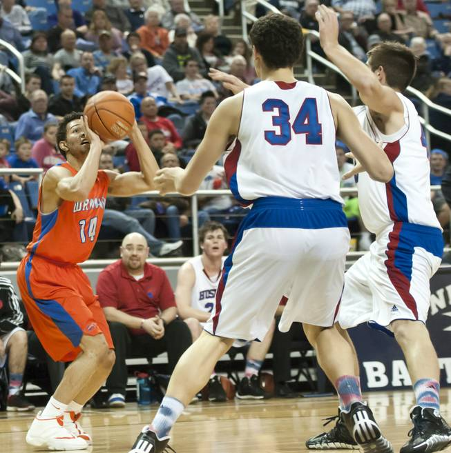 Noah Robotham pulls up for a fading jumper in the eyes of two defenders Thursday, Feb. 27, 2014 as Bishop Gorman defeats Reno 68-27 in the semifinals of the Nevada State Championships at Lawlor Events Center in Reno.