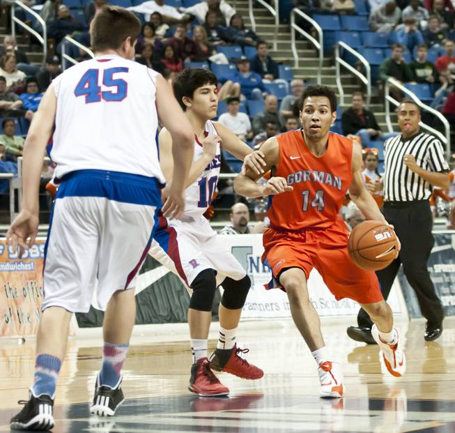 Noah Robotham knifes through the lane between defenders Thursday, Feb. 27, 2014 as Bishop Gorman defeats Reno 68-27 in the semifinals of the Nevada State Championships at Lawlor Events Center in Reno.