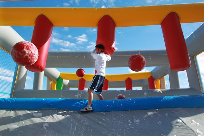 A participant makes his way across a sudsy bridge while balls are thrown at him during the Hit and Run 5k Saturday, March 1, 2014 at Sam Boyd Stadium. The Hit and Run 5k, a fun run with various obstacles to navigate, is being held or planned in two dozen cities across the country.