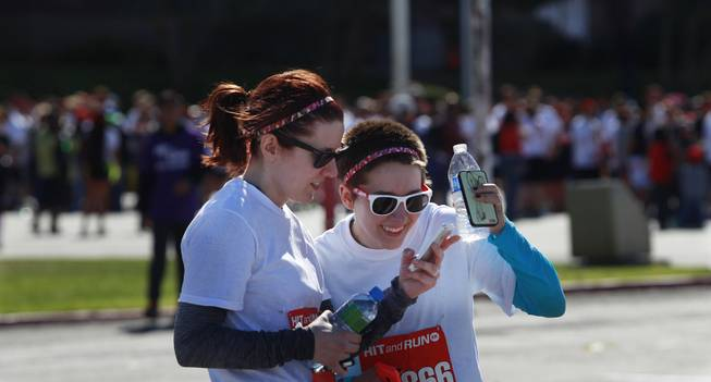 Torri Lippacher, left, and Ria Farmer look at video they shot of themselves participating in the Hit and Run 5k Saturday, March 1, 2014 at Sam Boyd Stadium. The Hit and Run 5k, a fun run with various obstacles to navigate, is being held or planned in two dozen cities across the country.