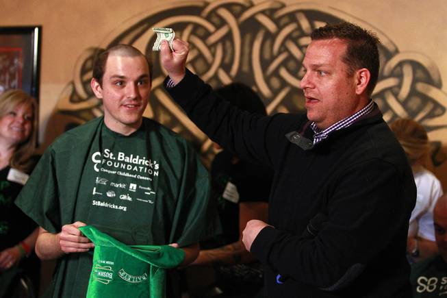 Cory Harwell, right, counts extra money that Nicholas Fortin has collected during the St. Baldrick's Day head-shaving fundraiser for cancer Saturday, March 1, 2014, at McMullan's Irish Pub.