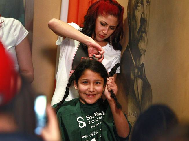 Victoria Lopez-Sosa holds up a braid during the St. Baldrick's head shaving fundraiser for cancer Saturday, March 1, 2014 at McMillan's Irish Pub. Lopez-Sosa was saving her hair to donate to Locks of Love.