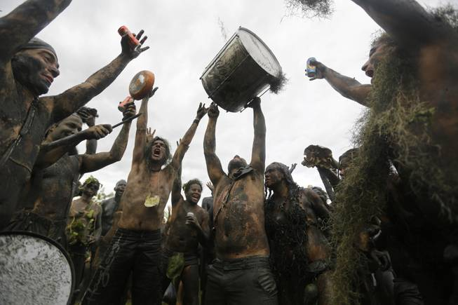 "Mud-covered revelers dance and sing at the ""Bloco da Lama"" or ""mud street party"" beneath an overcast sky in Paraty, Brazil, Saturday, March 1, 2014. The ""Bloco da Lama"" was founded in 1986 by two local teens who became local Carnival sensations after they appeared in the city's historic downtown covered in mud following a crab hunting expedition in a nearby mangrove forest, said Diana Rodrigues, who was hired by Paraty's City Hall to explain the history of the ""bloco"" to foreigners."