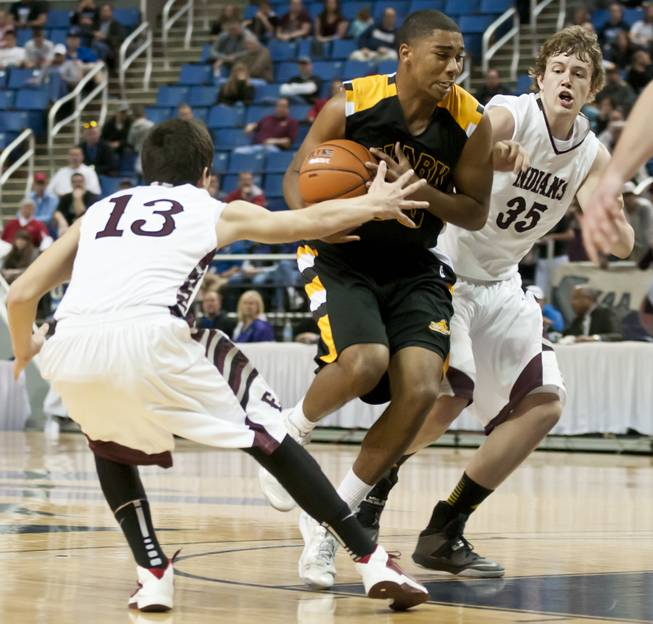 Sherron Wilson knifes into the lane before dishing to a teammate Saturday, March 1, 2014 as Clark High School defeated Elko High School 43-25 winning the Division I-A state championship at Lawlor Event Center in Reno.
