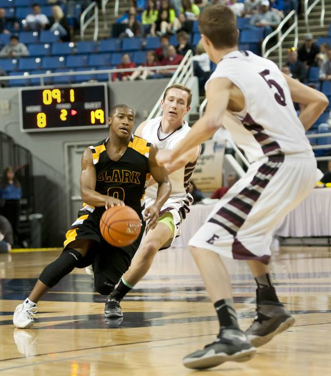 Colby Jackson gets between two defenders before dumping the ball off to a teammate for a score Saturday, March 1, 2014 as Clark High School defeated Elko High School 43-25 winning the Division I-A state championship at Lawlor Event Center in Reno.