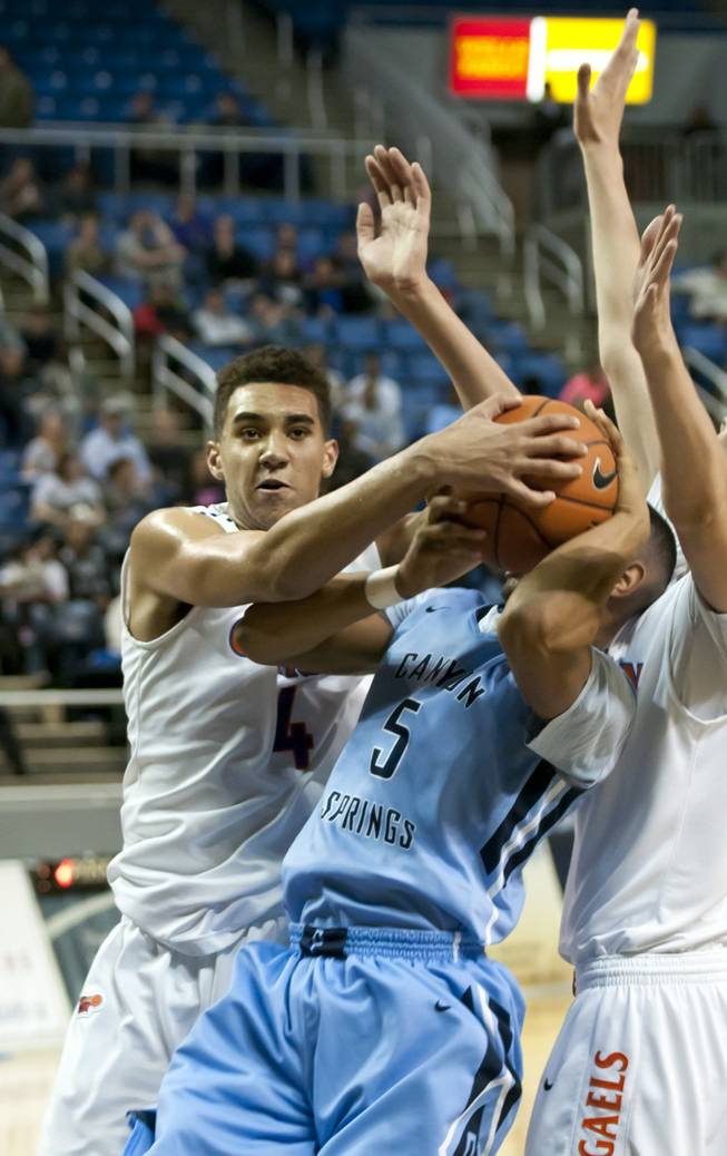 Chase Jeter, right, gets his hand on the ball forcing a jump ball Friday, Feb. 28, 2014 as Bishop Gorman defeated Canyon Springs 71-58 in the Nevada state championship game at Lawlor Event Center in Reno.