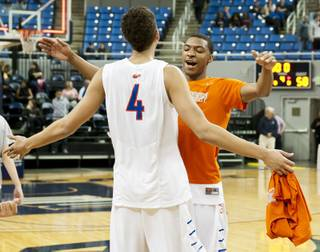 Bishop Gorman teammates celebrate after the final buzzer Friday, Feb. 28, 2014 as Bishop Gorman defeated Canyon Springs 71-58 in the Nevada state championship game at Lawlor Event Center in Reno.