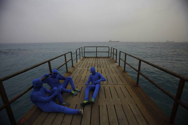 Men in the blue costumes are seen at a pier during the traditional parade to mark the end of the carnival period, in the southern port city of Limassol, southern of capital Nicosia, Cyprus, Sunday, March 2, 2014. Thousands of people gather every year to celebrate the Carnival in the streets.