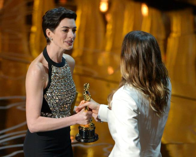 Anne Hathaway, left, presents Jared Leto with the award for best actor in a supporting role for Dallas Buyers Club during the Oscars at the Dolby Theatre on Sunday, March 2, 2014, in Los Angeles.  (Photo by John Shearer/Invision/AP)