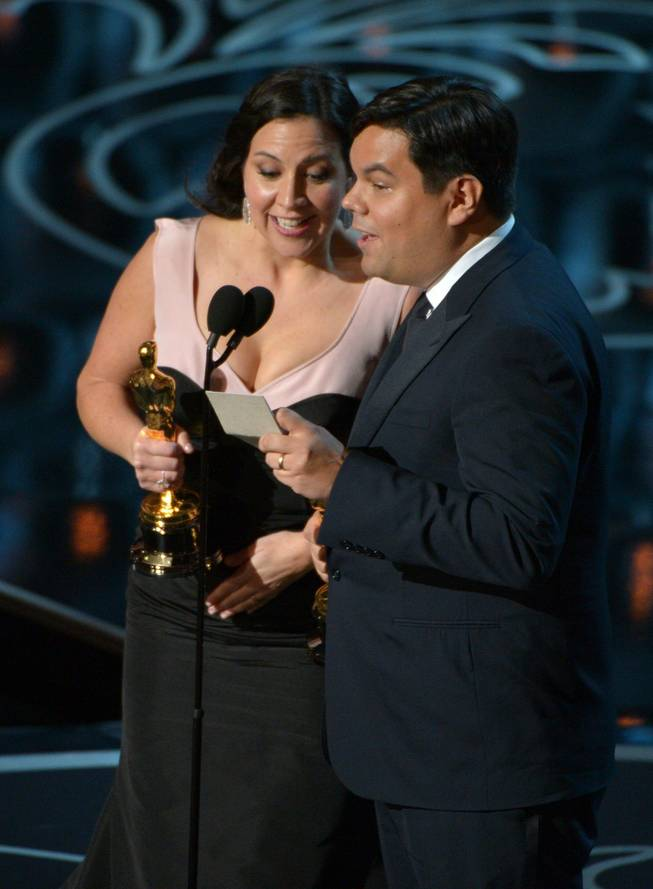 "Kristen Anderson-Lopez, left, and Robert Lopez accept the award for an original song in a feature film for ""Let It Go"" from ""Frozen"" during the Oscars at the Dolby Theatre on Sunday, March 2, 2014, in Los Angeles.  (Photo by John Shearer/Invision/AP)"