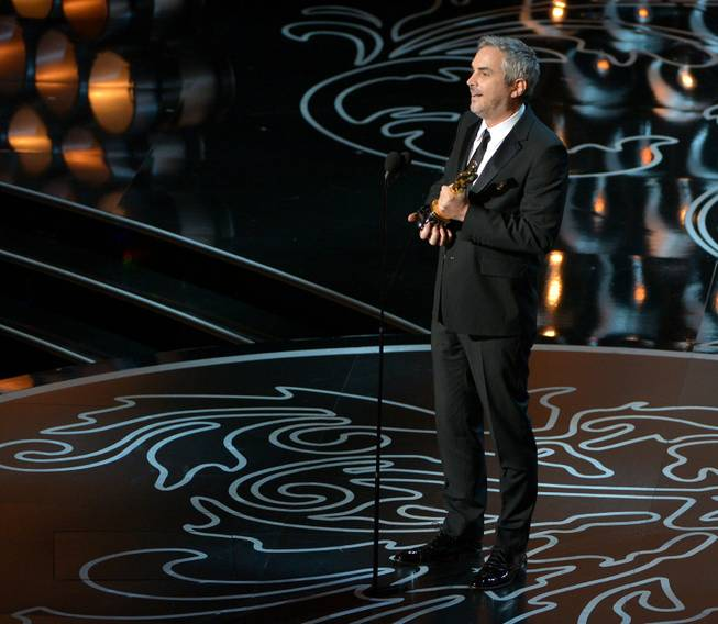 "Alfonso Cuaron accepts the award for best director of the year for ""Gravity"" during the Oscars at the Dolby Theatre on Sunday, March 2, 2014, in Los Angeles.  (Photo by John Shearer/Invision/AP)"
