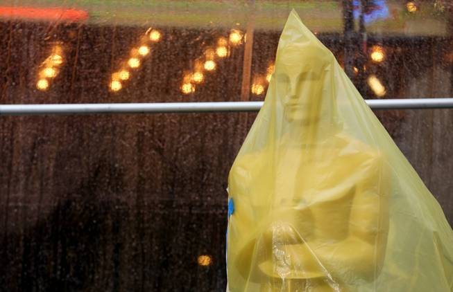 An Oscar statue covered in plastic stands on the red carpet as preparations are made during rainy weather for the 86th Academy Awards in Los Angeles, Friday, Feb. 28, 2014. The Academy Awards will be held at the Dolby Theatre on Sunday, March 2.