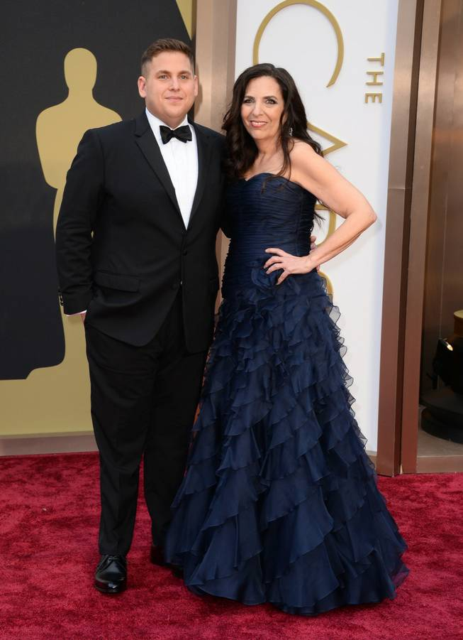 Jonah Hill, left, and Sharon Lyn Chalkin arrive at the Oscars on Sunday, March 2, 2014, at the Dolby Theatre in Los Angeles.  (Photo by Jordan Strauss/Invision/AP)