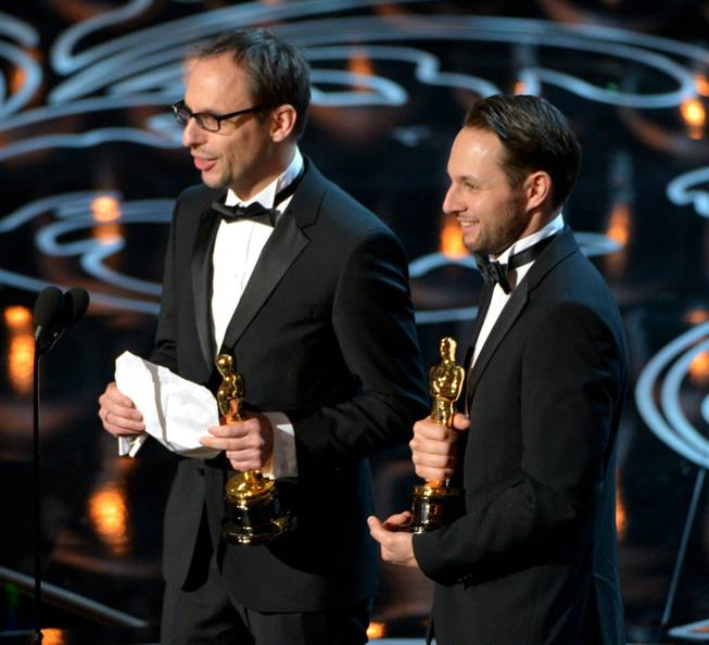 "Laurent Witz, left, and Alexandre Espigares accept the award for best animated short film of the year for ""Mr. Hublot"" during the Oscars at the Dolby Theatre on Sunday, March 2, 2014, in Los Angeles.  (Photo by John Shearer/Invision/AP)"