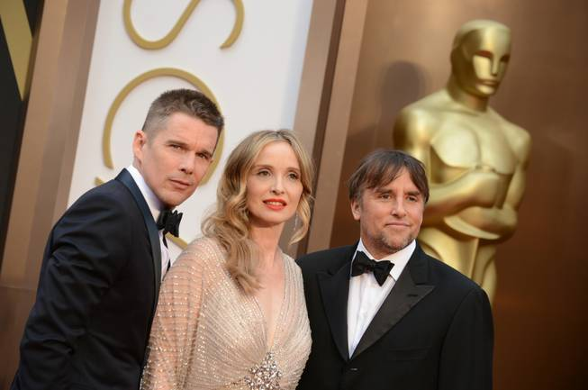 From left, Ethan Hawke, Julie Delpy and Richard Linklater arrive at the Oscars on Sunday, March 2, 2014, at the Dolby Theatre in Los Angeles.  (Photo by Jordan Strauss/Invision/AP)