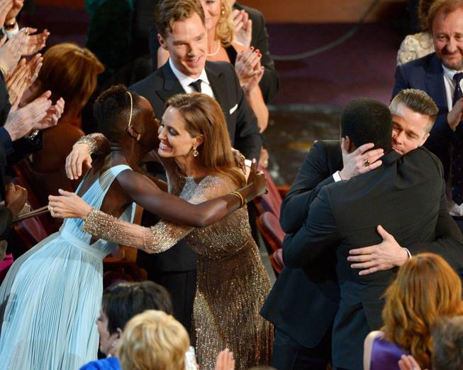 "Lupita Nyong'o, left, is embraced by Angelina Jolie, and Brad Pitt embraces Chiwetel Ejiofor as they celebrate in the audience after ""12 Years a Slave"" was announced the winner for best picture during the Oscars at the Dolby Theatre on Sunday, March 2, 2014, in Los Angeles.  (Photo by John Shearer/Invision/AP)"
