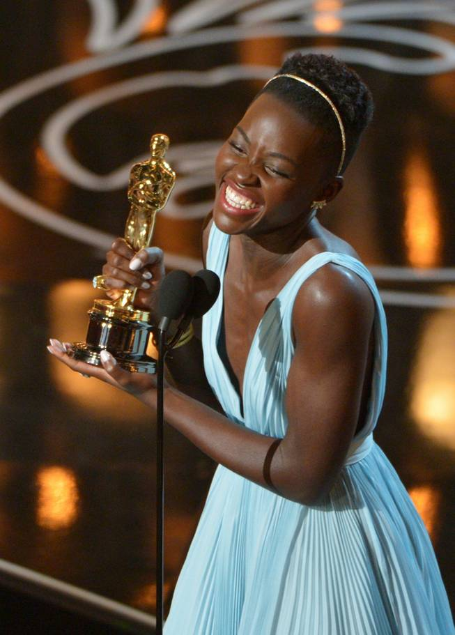 "Lupita Nyongo accepts the award for best actress in a supporting role for ""12 Years a Slave"" during the Oscars at the Dolby Theatre on Sunday, March 2, 2014, in Los Angeles.  (Photo by John Shearer/Invision/AP)"