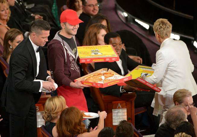 Brad Pitt, left, and Ellen DeGeneres, right, pass out pizza in the audience during the Oscars at the Dolby Theatre on Sunday, March 2, 2014, in Los Angeles.  (Photo by John Shearer/Invision/AP)