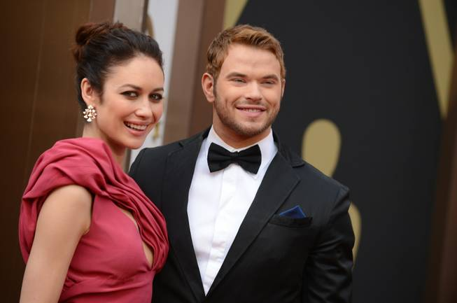 Olga Kurylenko, left, and Kellan Lutz arrive at the Oscars on Sunday, March 2, 2014, at the Dolby Theatre in Los Angeles.  (Photo by Jordan Strauss/Invision/AP)
